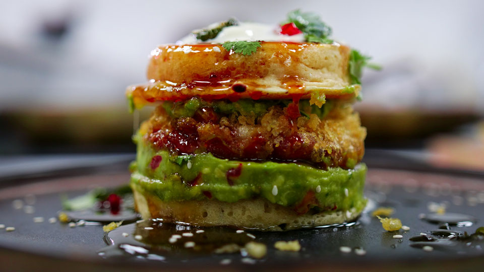 Meatless Sausage patty on a bed of avocado, sandwiched between two pancakes